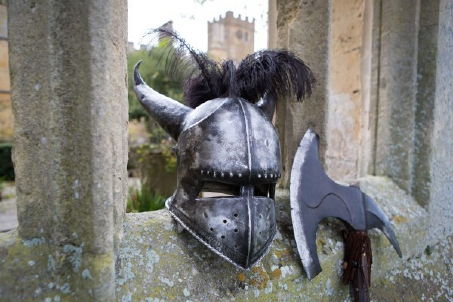 A medieval helmet and axe sit perched on a wall