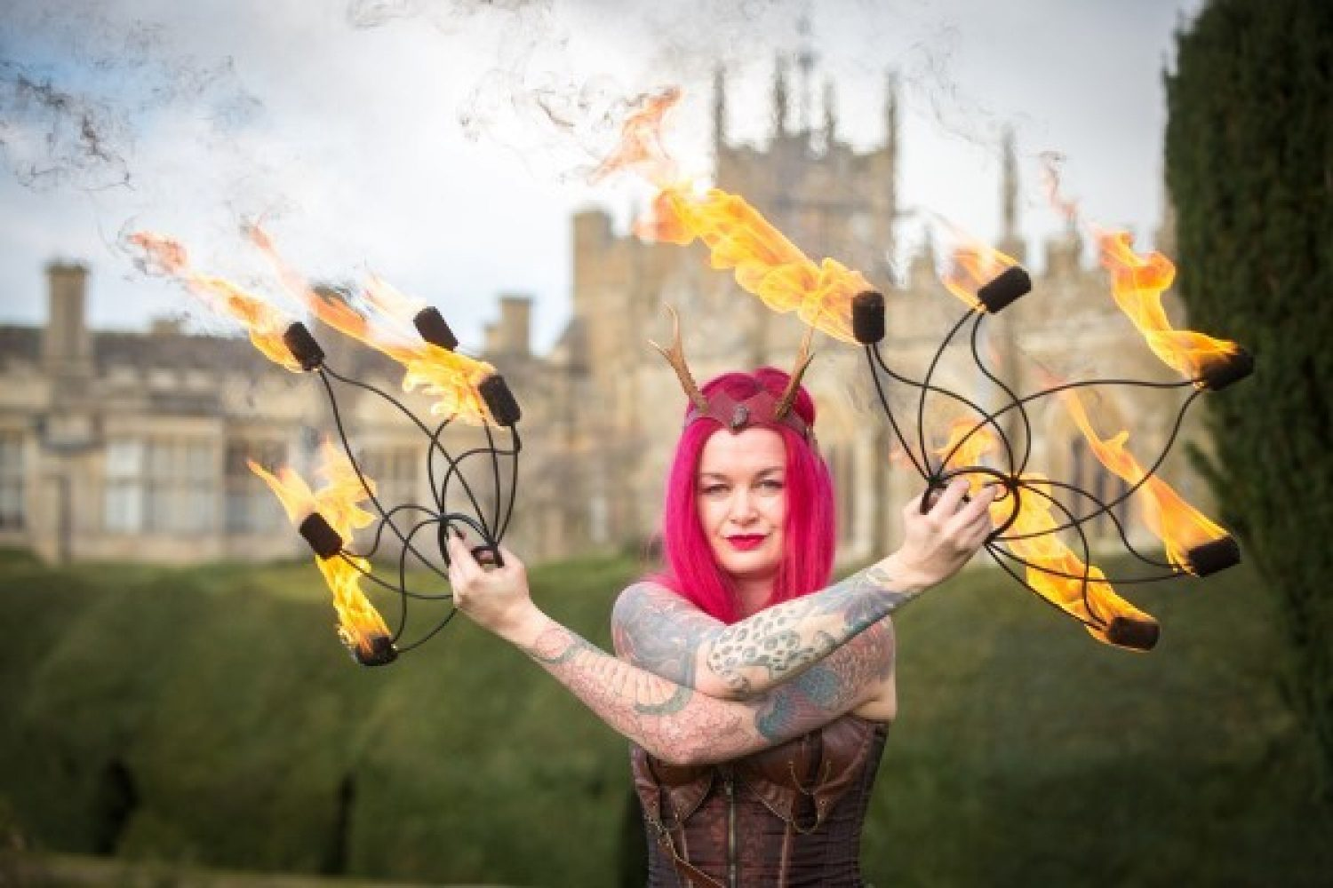 A female performer holds flaming objects