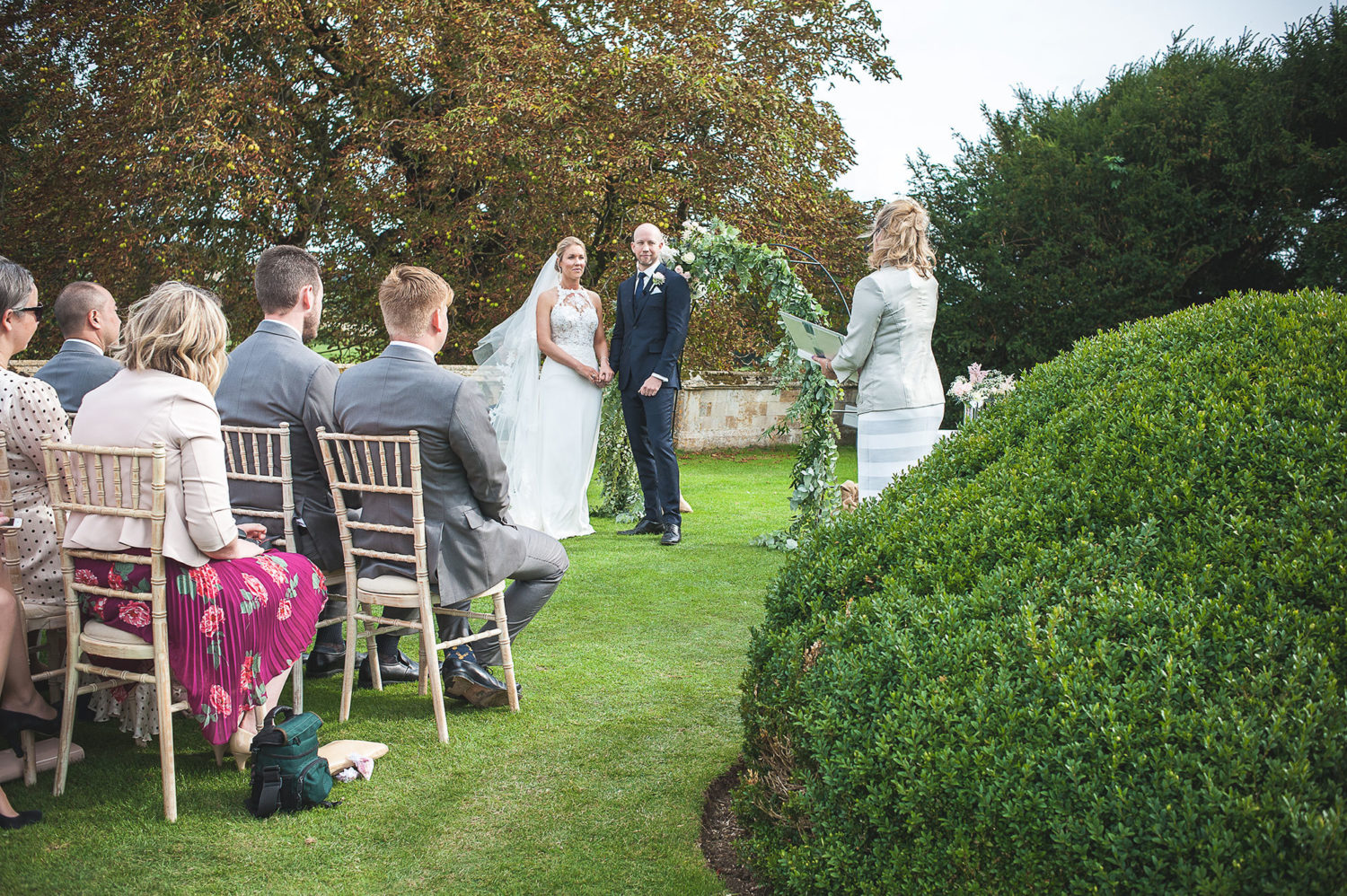 A couple stand hand-in-hand on a lawn in front of seated guests