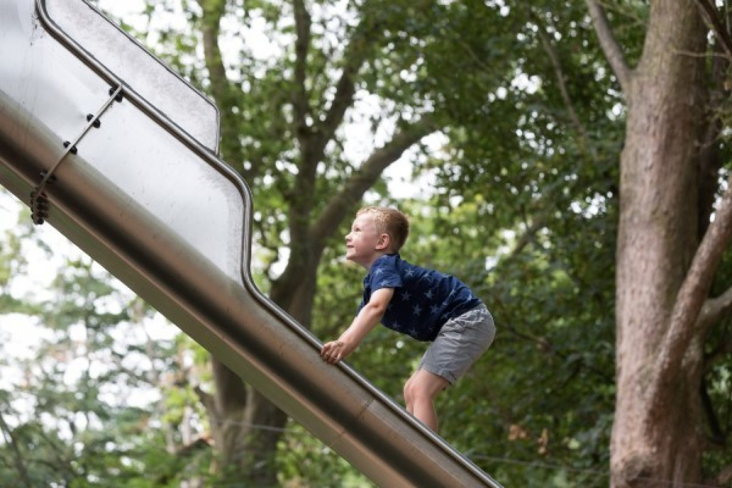 A boy climbs up a metal slide
