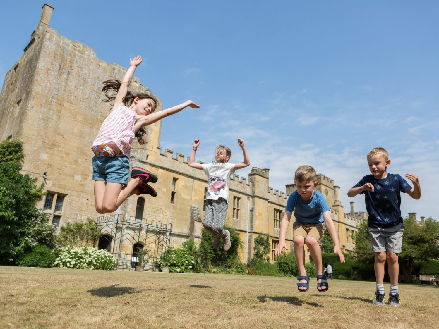 children jumping in air in front of castle