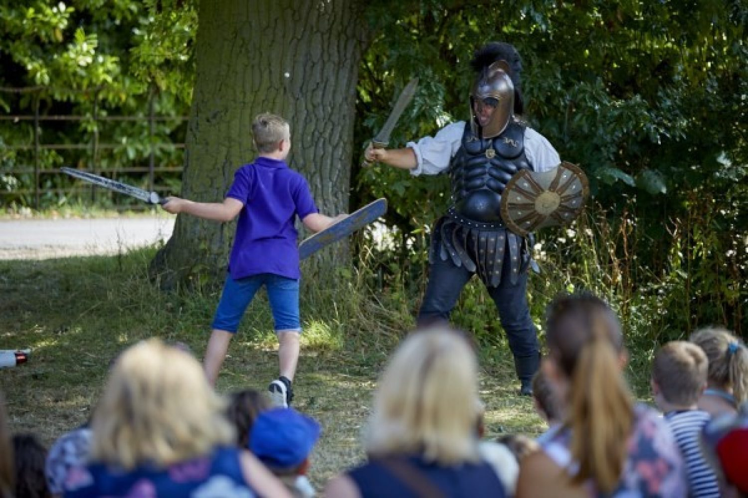 A young boy engages in a mock fight with an entertainer clad in Roman armour