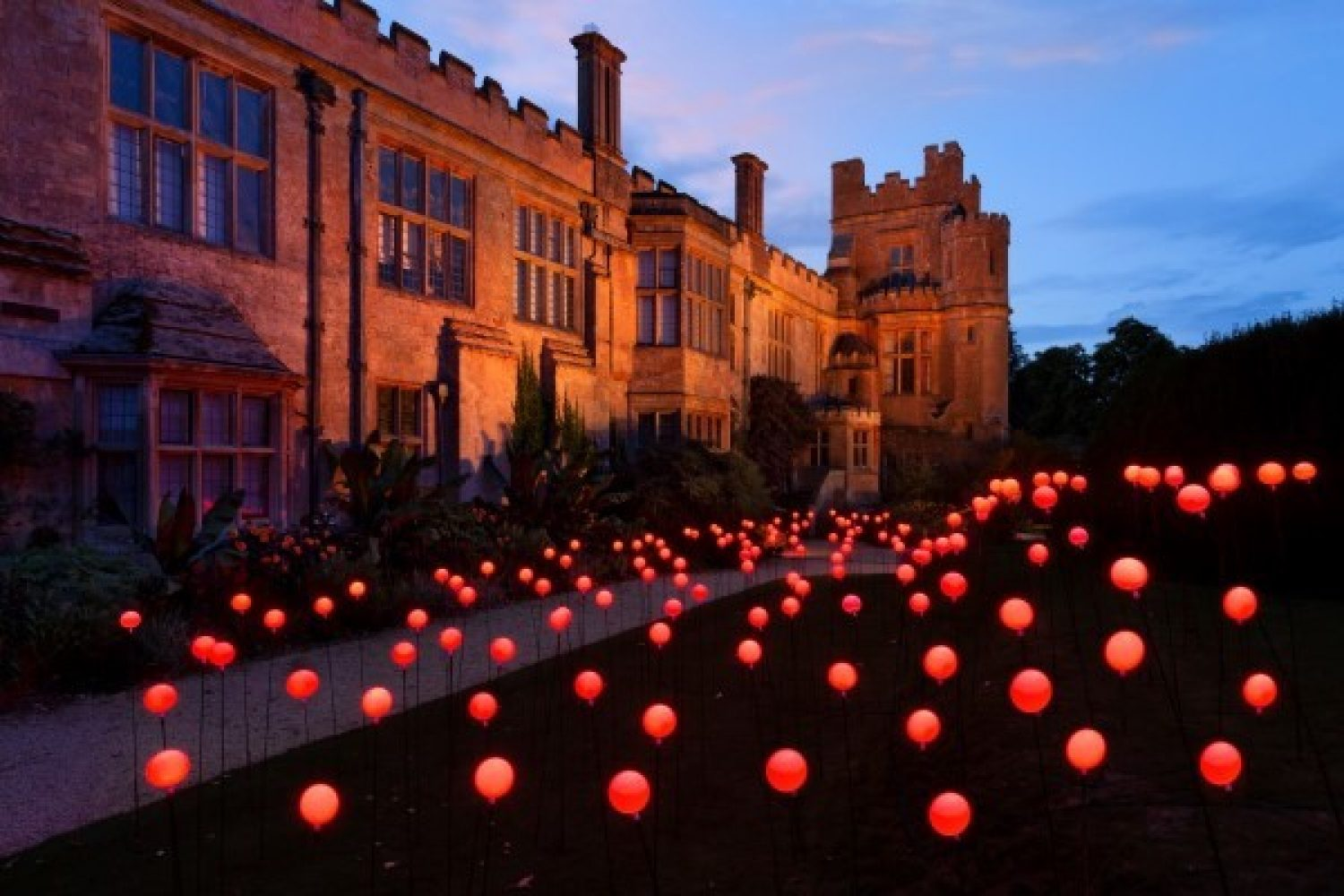 Dusk shot of field of illuminated poppies outside exterior of Sudeley Castle