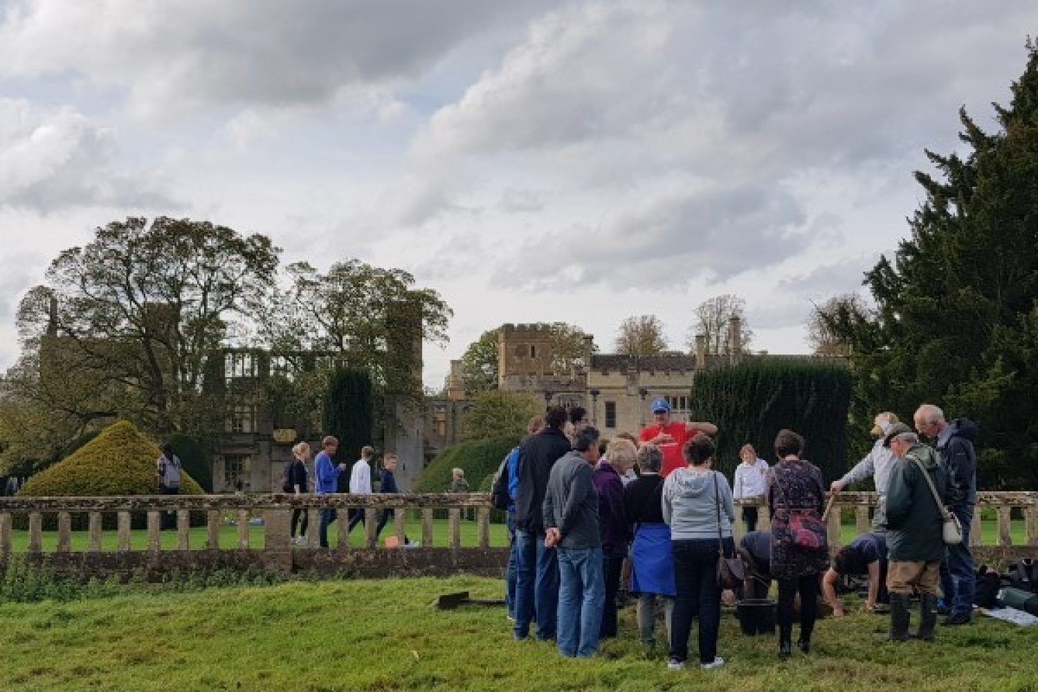 A group of visitors surround one of the dig sites