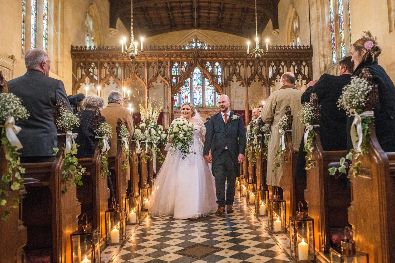 Newly married couple walk down chapel aisle