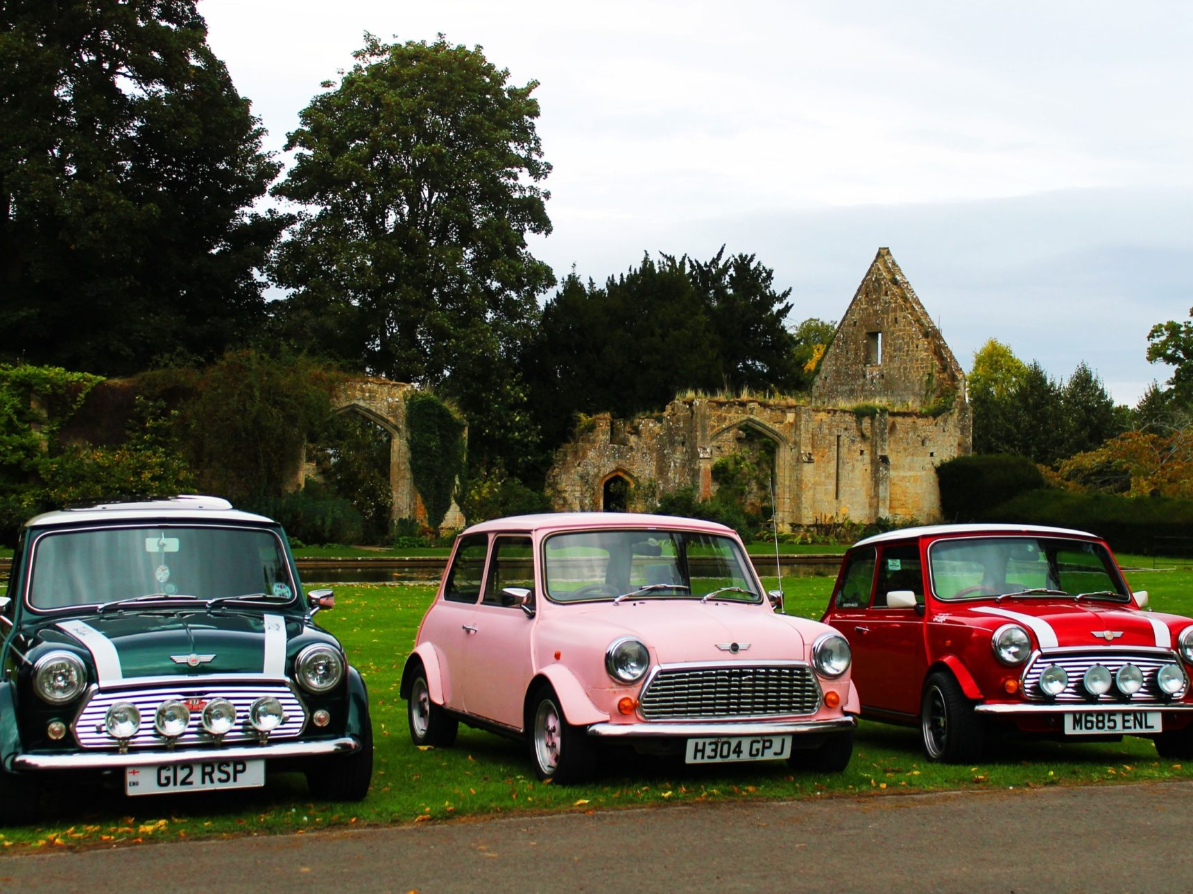 Green, pink and red Mini Coopers sit side by side