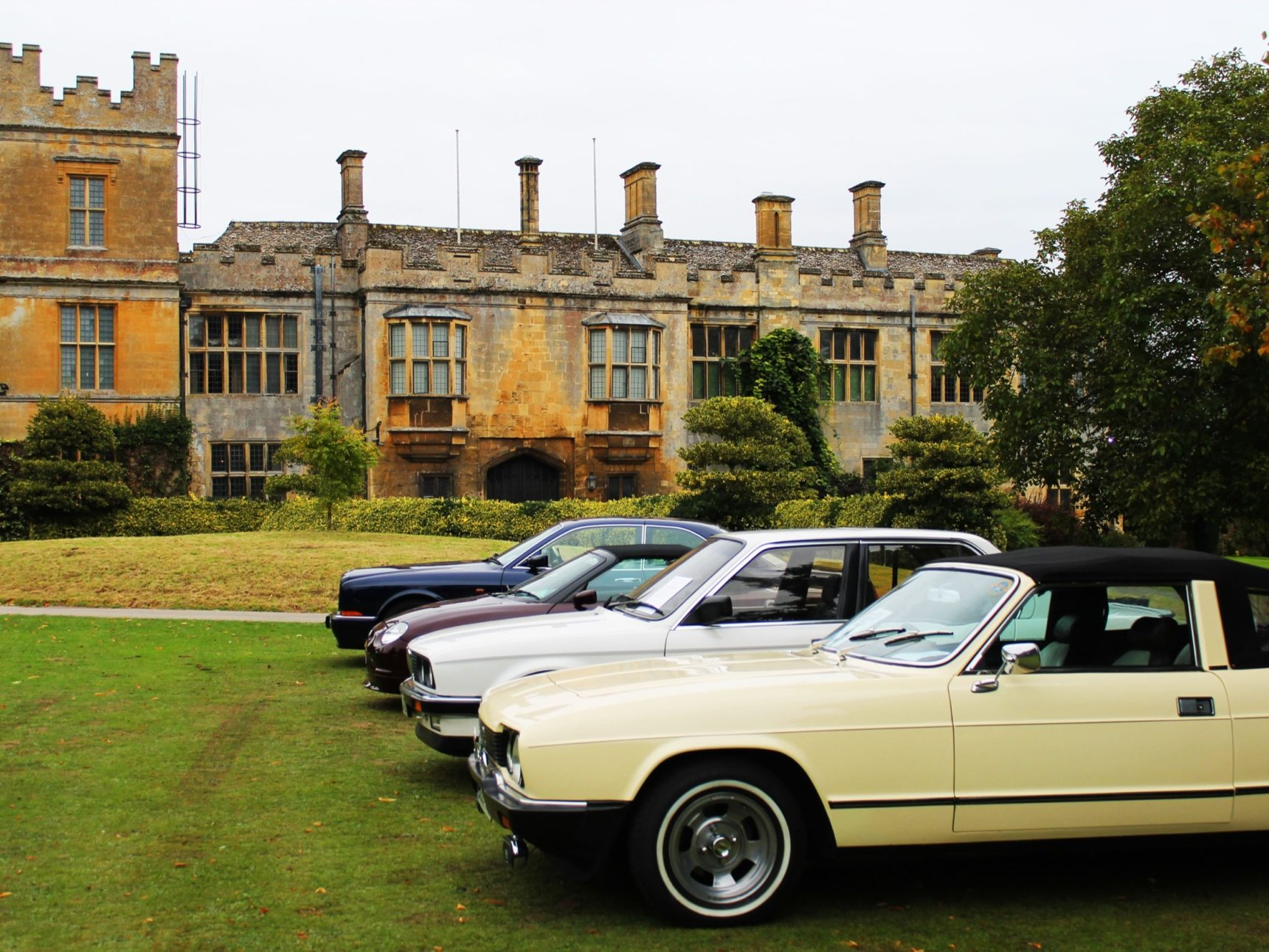 A selection of vintage cars sit on the lawn in front of the castle