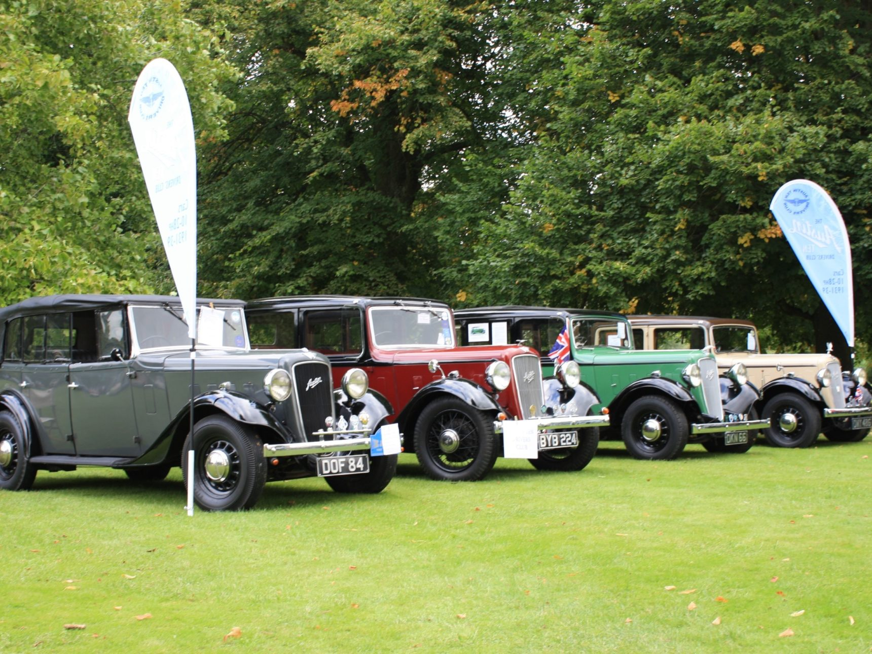 A selection of vintage cars sit on the law in between 2 banners