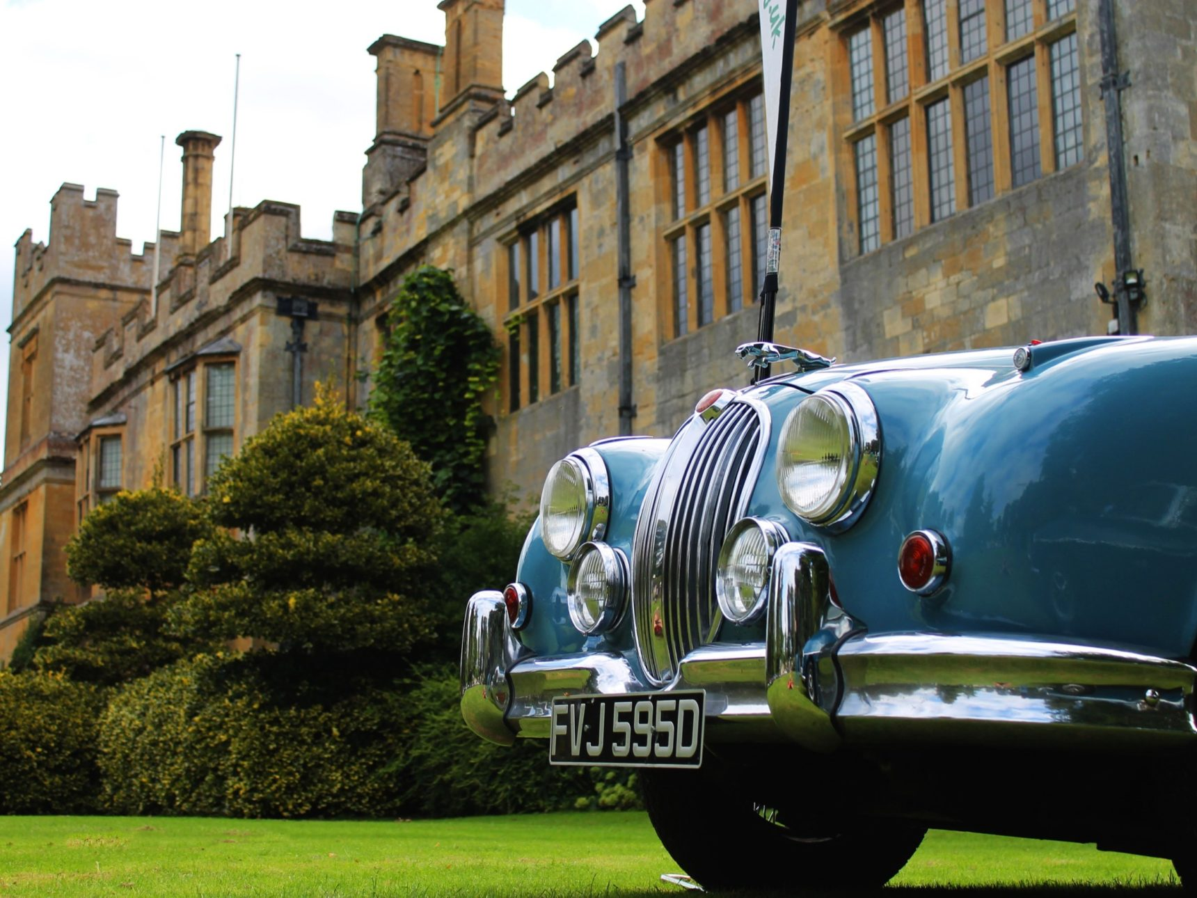 A close up shot of a teal coloured vintage car in front of the castle