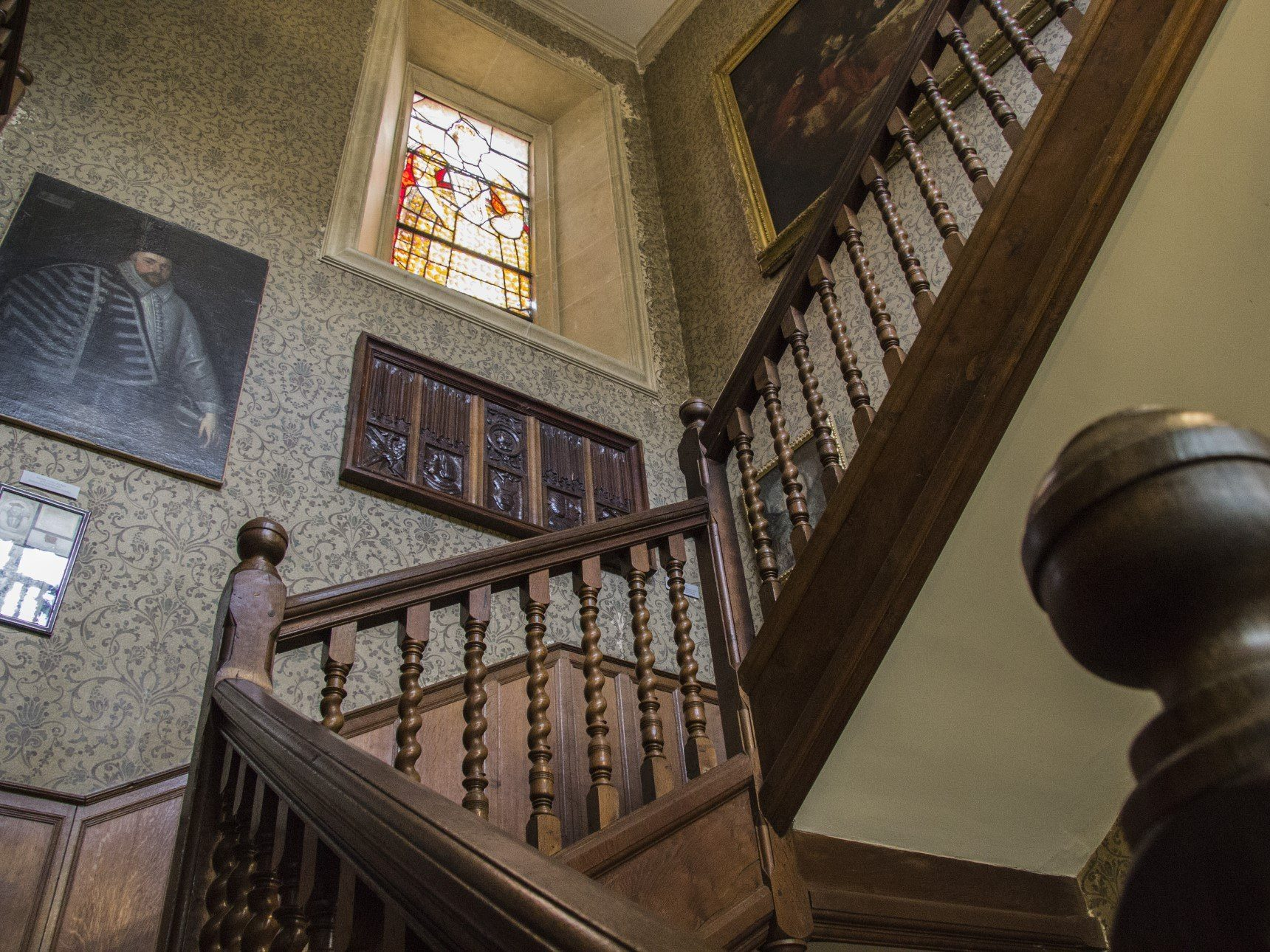 View looking upstairs in South Hall showing a number of paintings on the wall and a stained glass window of Elizabeth I