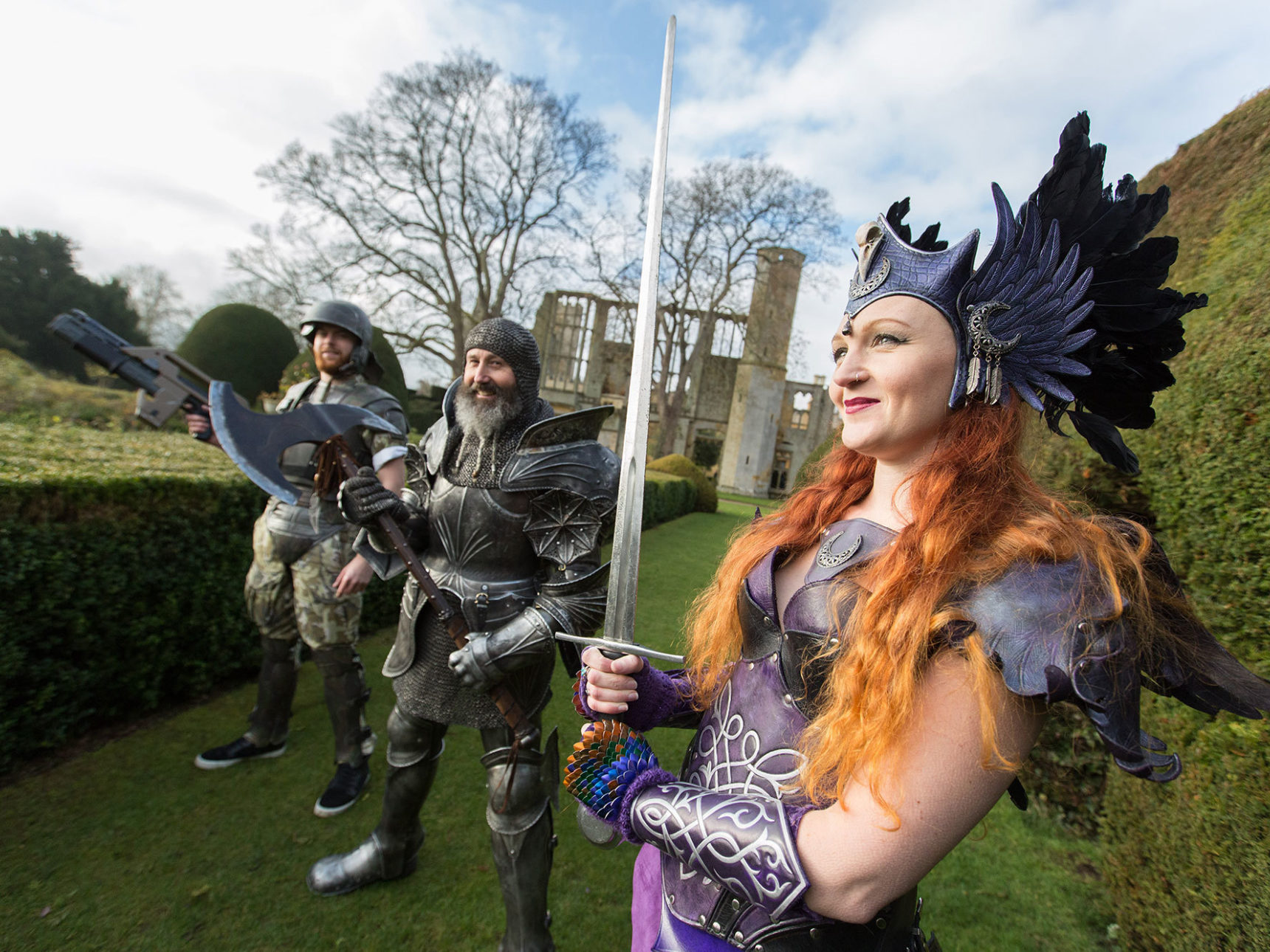 Performers clad in medieval armour stand in gardens