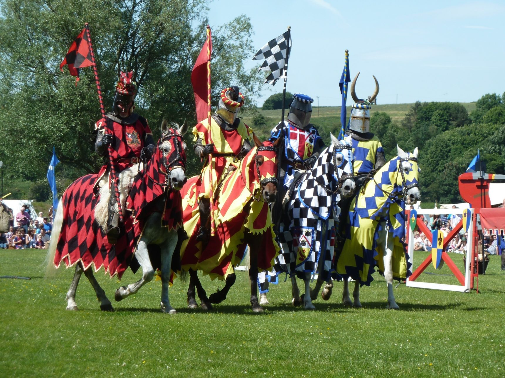 4 mounted knights dressed in medieval costume stand side by side
