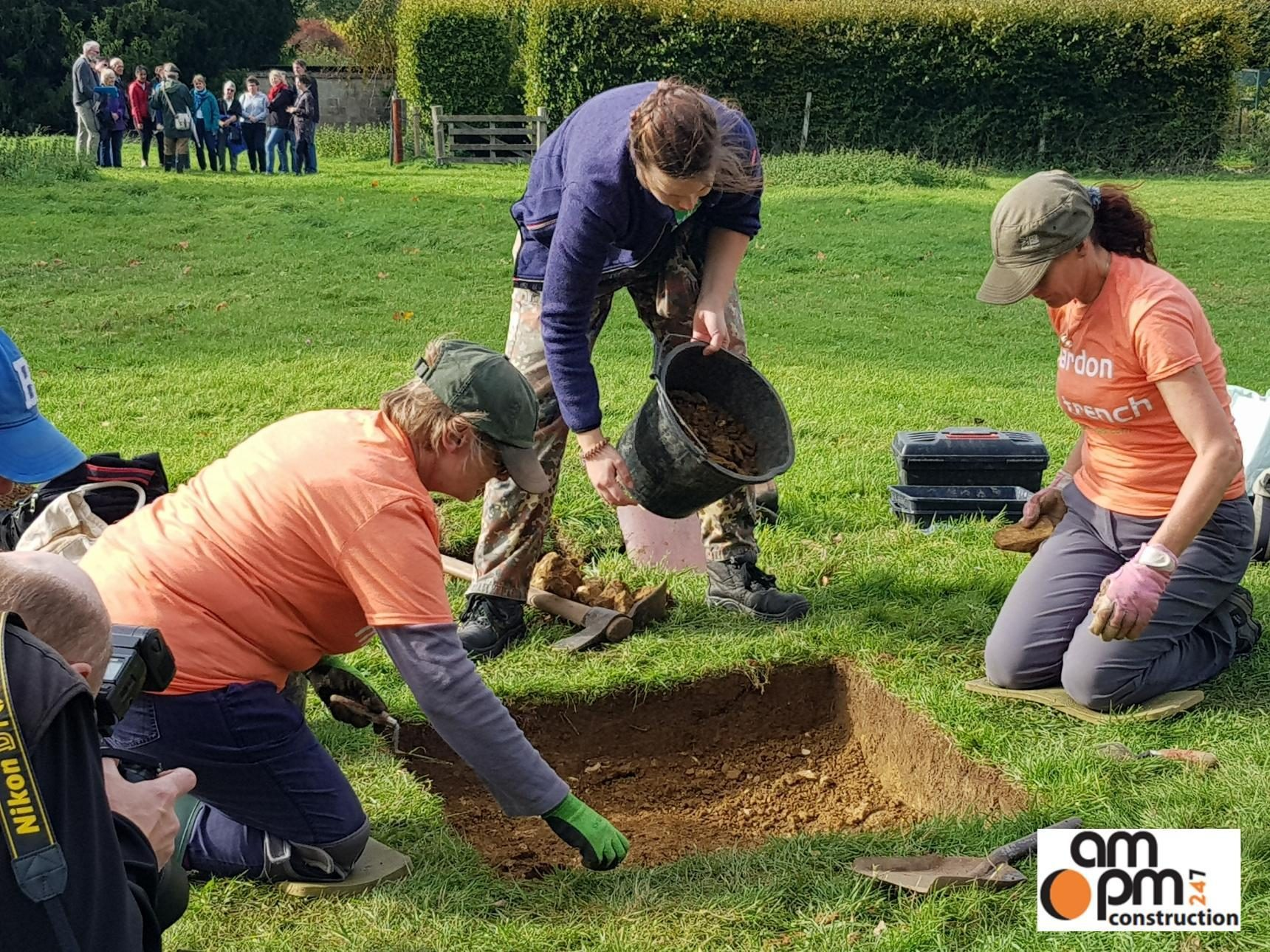 3 people sort through a small square dig site