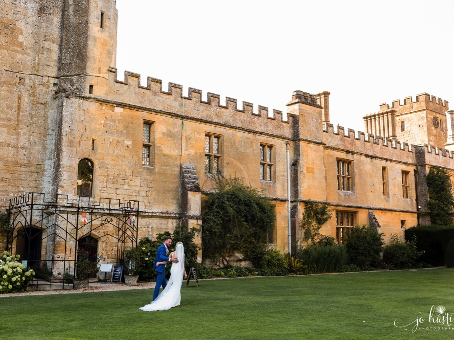 Wedding couple walking along Mulberry Lawn with Castle backdrop